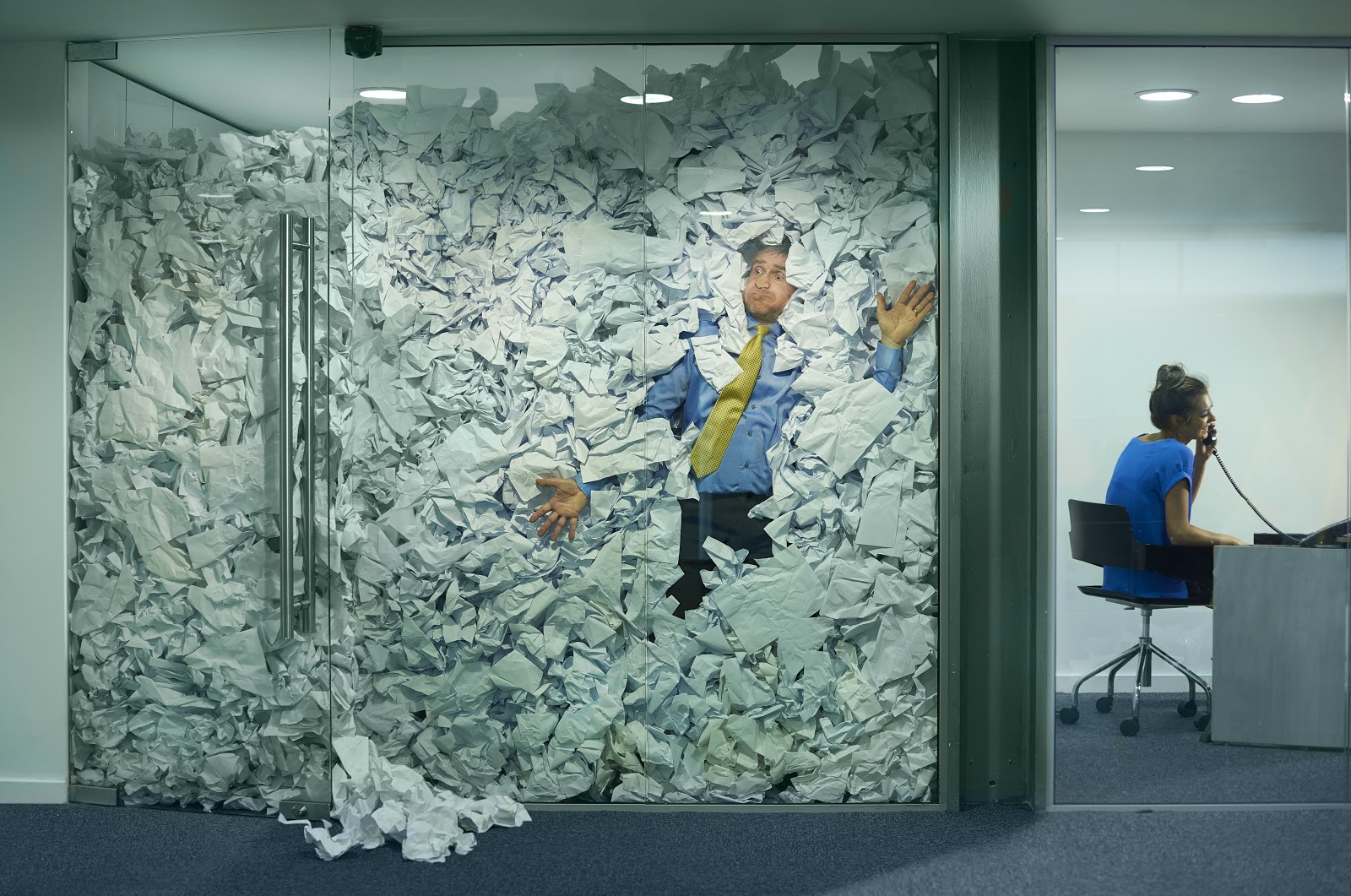 a man in an office with paper full to the ceiling