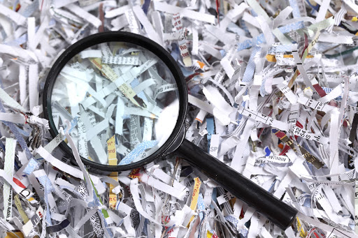 a magnifying glass in a pile of shredded paper
